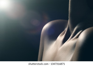 beautiful female slim neck with clavicle on black background with light flare