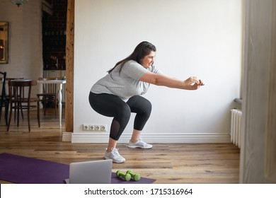 Beautiful female in sneakers and sports clothes exercising indoors, doing squats to burn fat, lose extra pounds, making body strong, watching instructional videos on laptop. Technology and fitness