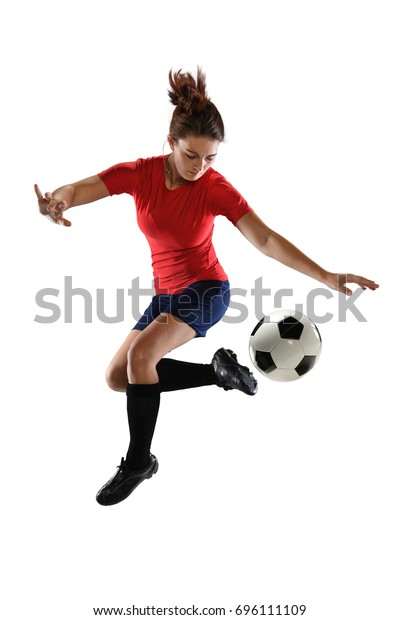 Beautiful female soccer player kicking ball with heel isolated over white background