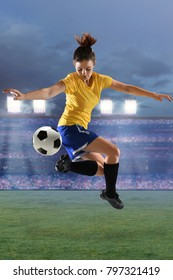 Beautiful female soccer player performing back kick inside stadium