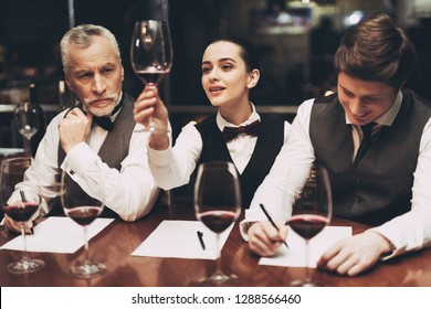 Beautiful female sommelier is holding glass of wine and tasting sediments. Confident sommelier tasting wine in restaurant