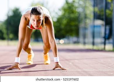 Beautiful female sprinter getting ready for the run during summer