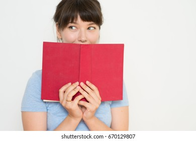 Beautiful female student with glasses reading a red book isolated on background