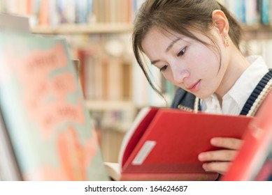 Beautiful female student reading a red covered book on a bookshelf in library