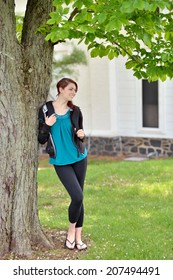 Beautiful female student, with red hair, carrying a back pack and book as stands near a tree on campus