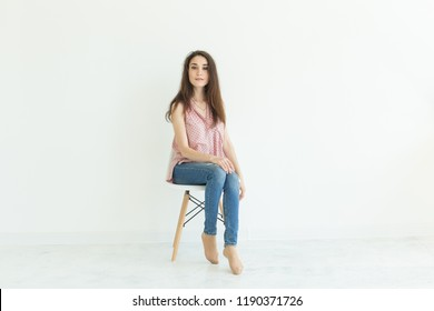 Beautiful female student sitting on a chair on white background with copy space