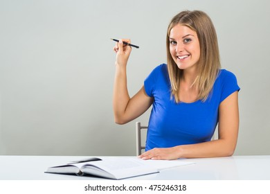Beautiful female student sitting at the table and pointing with pen.  Beautiful female student pointing with pen