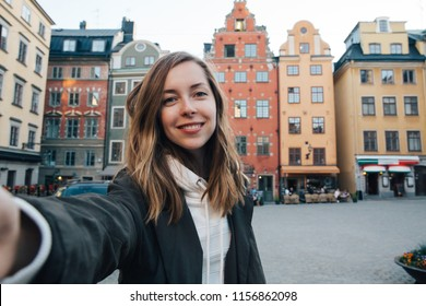 Beautiful female student taking selfie portrait in Bruges old town, Belgium. Cheerful girl blogger takes photo for social media.