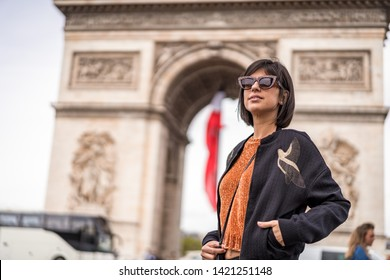 Beautiful female with sunglasses standing next to Arc de Triomphe in Paris France waiting for taxi on street. Triumphal arch