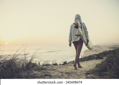 Beautiful female Surfer looking for the waves