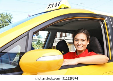 Beautiful female taxi driver sitting in car
