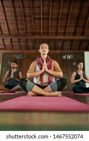 Beautiful female teacher giving meditation course to two multi-ethnic men on yoga mats in traditional temple in Bali Indonesia