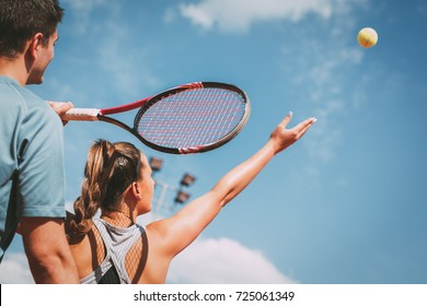 Beautiful female tennis player with instructor practicing serve on outdoor tennis court.