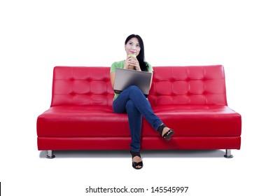 Beautiful female thinking of something while drinking coffee on sofa, isolated on white