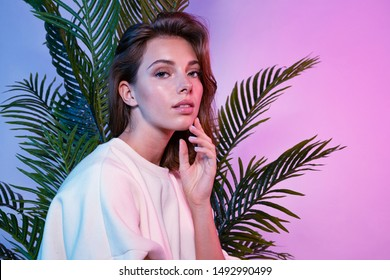 Beautiful female touching face with tenderness. Lady sitting near green palm tree and looking at camera with tenderness. Beauty and fashion concept