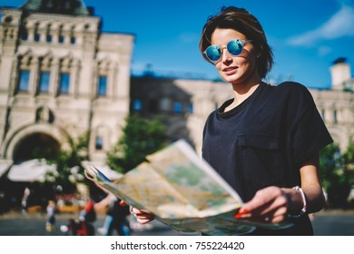 Beautiful female tourist dressed in casual clothes enjoying vacation holidays in sunny city and looking for exciting places.Young pondering woman searching sightseeing on guide map during strolling