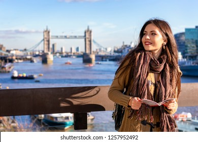 Beautiful female tourist in London holding a city map in front of the Tower Bridge on a sunny day, UK