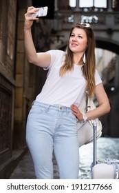 Beautiful female tourist making selfie on the background of landmark