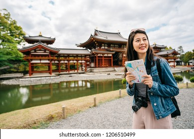 beautiful female tourist relaxing standing near the red temple holding the map and smile cheerfully. traveler finding direction on the paper map. lady with sunglasses on head traveling in Japan.