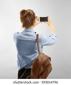 Beautiful female tourist taking photo with mobile phone, on light background