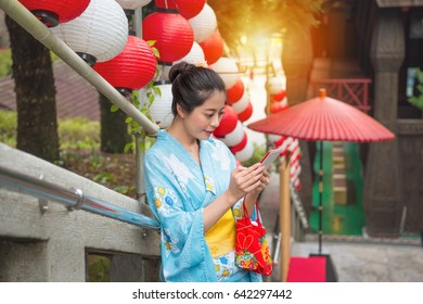 beautiful female tourist wearing traditional kimono join japanese celebration festival resting on lantern decorations area and using mobile smartphone texting searching guide in summer vacation.