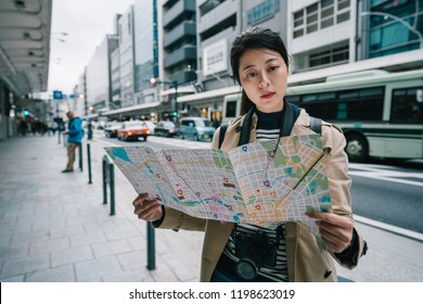 beautiful female traveler holding the map and finding the right direction back to hotel in Japan. backpacker travel in Kyoto lifestyle. asian female model traveling.