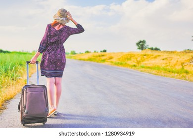 Beautiful female traveler in summer dress and hat hitchhiking with suitcase. Cute woman walking on the road with Luggage. Journey concept