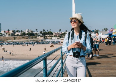 a beautiful female traveler walking nearby the beach and watching beautiful views with her phone on her hand