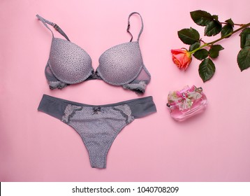 Beautiful female underwear. Lace panties and bra lying on the pink background.