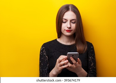 Beautiful female user mobile phones on a yellow background. Dependence on smartphone