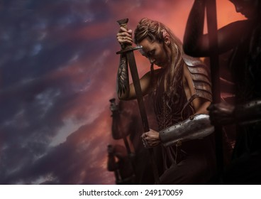 Beautiful female warrior elf with sword over cloudy sky