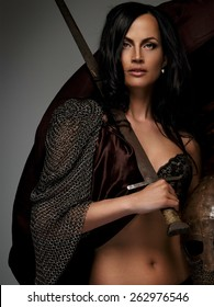 Beautiful female warrior holding sword and helmet