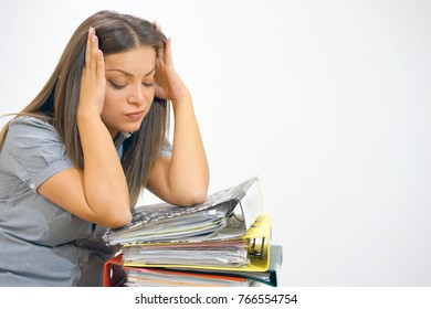 Beautiful female worker is distressed with a lot of paperwork in front of her. A lot of paper work in office.