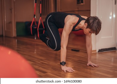 Beautiful female workout pilates and yoga instructor doing exercises with suspension tracks TRX