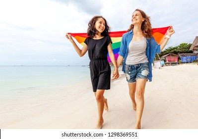 beautiful female young lesbian couple in love walks along the beach with a rainbow flag, symbol of the LGBT community, equal rights, beauty and love