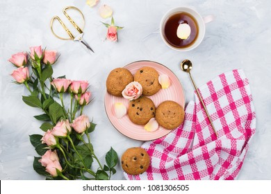 Beautiful feminine flatlay with cup of black tea, cookies, towel and bouquet of pink roses, cement background
