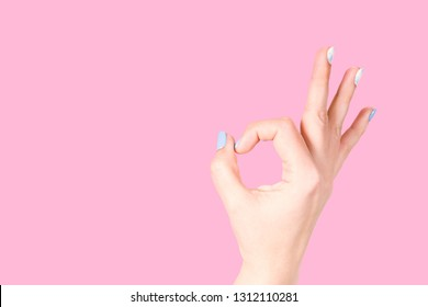 Beautiful fenale hand with trendy colorful blue and white fresh gel manicure. Woman showing okey sign isolated on pink background Horizontal color photography.