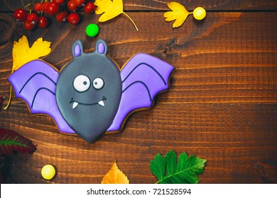 Beautiful festive background for Halloween with gingerbread, autumn leaves, berries and candy on a wooden table. Free space