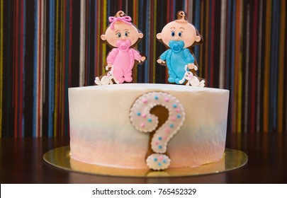 A beautiful festive biscuit cake with a question mark in front and sweet figures of a boy and girl in the center. Focus on the figures. Cake with a secret. Gender Reveal Party. Tasty boy or girl cake