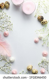 Beautiful festive Easter frame made with little white flowers, quail eggs, feathers and merengue cookies on light grey background. Copy space for your design. Eco friendly holiday decorations.