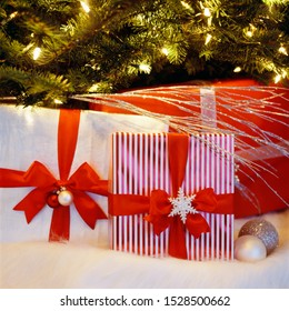 Beautiful, festive, fancy, wrapped Christmas gifts presents under lighted illuminated Christmas tree. Holidays at home.