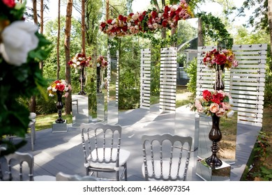 Beautiful festive place made with wooden square and floral roses decorations for outside wedding ceremony in park.Rustic wedding photo zone.