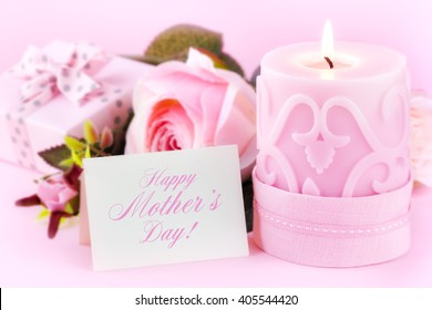 Beautiful festive setting with a Happy Mother's Day greeting card, lit candle, roses and a gift against pastel pink background. With copy space for your text