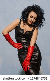 Beautiful fetish model wearing black spandex dress and long red leather gloves posing near blue wall.
