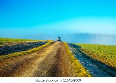 Beautiful field path with car in beautiful landscape.
