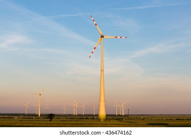 Beautiful fields surrounding windmills on the field during summer day with blue sky
