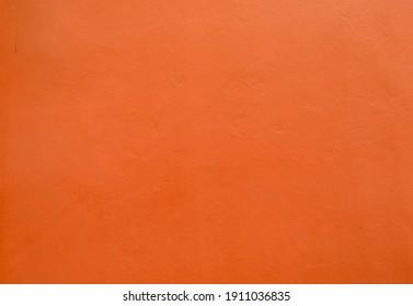 Beautiful fiery red-orange wall grunge cement, abstract texture. Orange color fun, warmth, fire, energy. Orange autumn hues degrade background vivid light top, dark bottom. Halloween background empty.