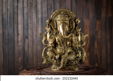 Beautiful figurine of Hindu god of wisdom, knowledge and new beginnings Ganesha against wooden background.