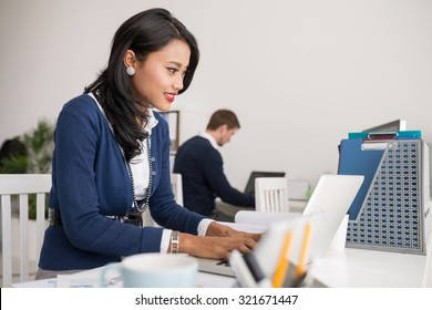 Beautiful Filipina business lady working on laptop in the office