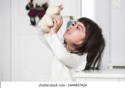 Beautiful Filipino girl playing with little teddy bear doll at home.